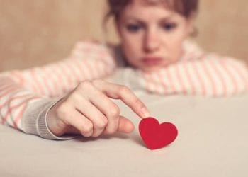 Sad girl is holding heart symbol by her finger and looking at it. Love and relationships concept