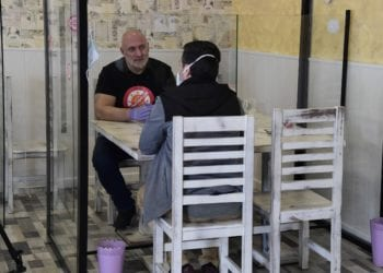 Manuel Gil (L), owner of the LLenatubar company, sits at a table with methacrylate partition walls built and installed by his company in a small restaurant in Leganes near Madrid on April 23, 2020. - Shops, bars, restaurants and other businesses considered nonessential remain closed in Spain amid a national lockdown to fight the spread of the coronavirus. (Photo by JAVIER SORIANO / AFP)