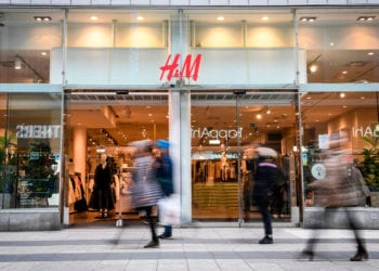 Shoppers walk past a fashion store of H&M (H & M Hennes & Mauritz AB) in central Stockholm on April 2, 2020. - Swedish retailer H&M said that the company have started dialogue with tens of thousands of staff about cutting working hours due to the coronavirus (Covid-19) pandemic effect on the market. (Photo by Fredrik SANDBERG / various sources / AFP) / Sweden OUT (Photo by FREDRIK SANDBERG/TT News Agency/AFP via Getty Images)