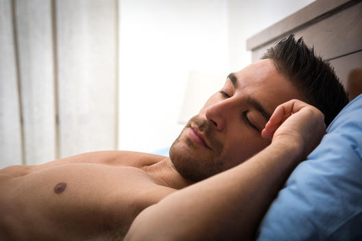 Handsome shirtless athletic young man laying in bed with eyes closed, sleeping