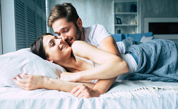 Couple in bed at home are kissing each other