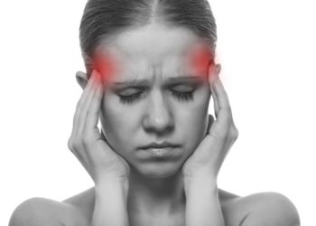 Woman having a migraine, isolated on white background, monochrome photo with red as a symbol for the hardening