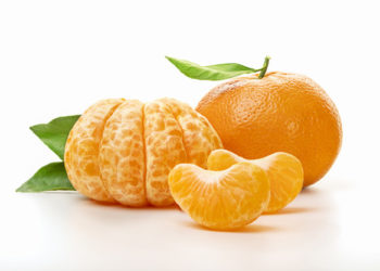 Isolated tangerines. Half of peeled tangerine and whole mandarin or orange fruit with green leaves isolated on white background. Close up.