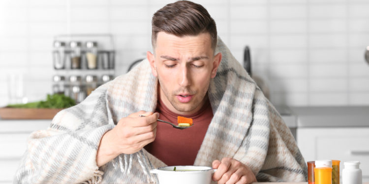 Sick young man eating broth to cure cold at table in kitchen; Shutterstock ID 1095168275; Job: GSK
