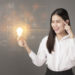 Intelligent woman is holding light bulb with business and financial  data