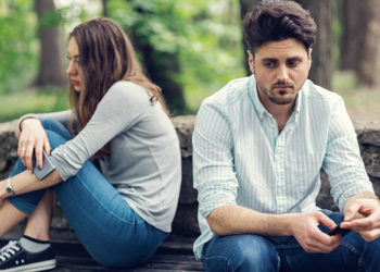 Young sad looking couple sitting at a distance and looking away from each other. Selective focus on the male.