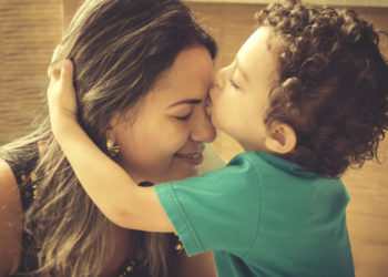 Little 2 years old boy, hugging and kissing his mother, with affectionate gesture.