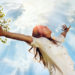 Pretty young woman raising her arms and enjoying perfect sunny day in nature. Her hair is long and bouncy, wearing a white shirt and enjoys smiling with eyes closed. Above her it is the sky with clouds through which spread sun rays. AdobeRGB color space. Small amount of grain added intentionally for better final impression.