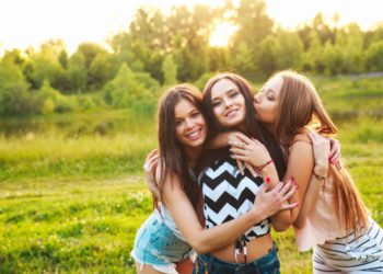 three beautiful girls walking and laughing on sunset in the park. Friendship concept. Summertime