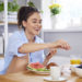 Young woman at home in kitchen, eating breakfast