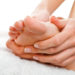 Woman making foot massage holding her foot with both hands on the white towel.r