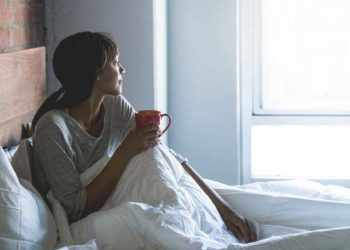 millennial African-American woman spending her morning in her bed, in her pajamas, with a warm mug of coffee, staring out the windown day dreaming or happily thinking to herself. 675090804