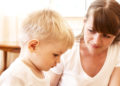 mother talking with her unhappy son at home; shallow DOF, focus on mothers eyes