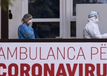 """Members of the University Clinical Center of Kosovo in protective gear walk past a sign reading """"Ambulance For Coronavirus"""" at the University Clinical Center of Kosovo in Pristina on March 14, 2020. - Kosovo reported its first coronavirus (COVID-19) case on March 13, 2020, in a 22-year-old Italian woman and a 77-year-old Kosovar man, both recently returned from Italy. (Photo by Armend NIMANI / AFP)"""